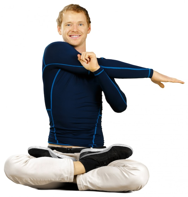 Flexibler sportlicher junger mann, der die übungen ausdehnend lokalisiert auf weiß tut Premium Fotos