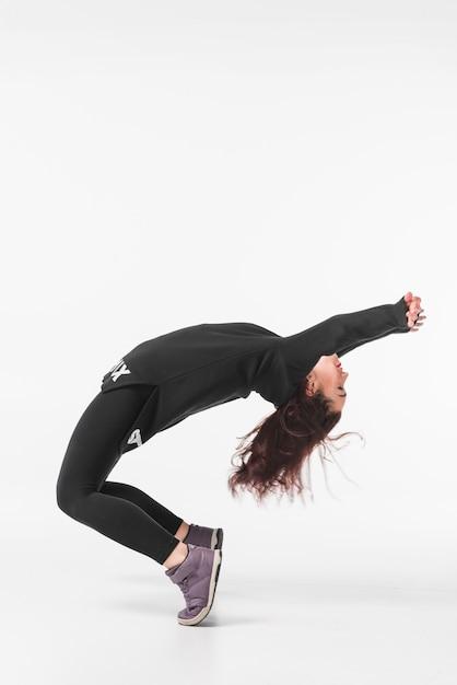 Flexibles tanzen der jungen frau gegen weißen hintergrund Kostenlose Fotos