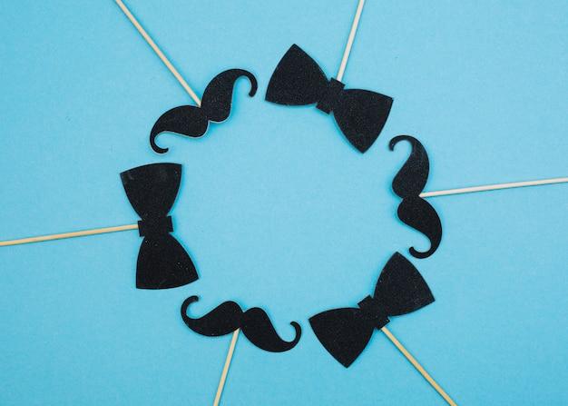 Fliege und schnurrbart auf zauberstäben in form eines kreises Kostenlose Fotos