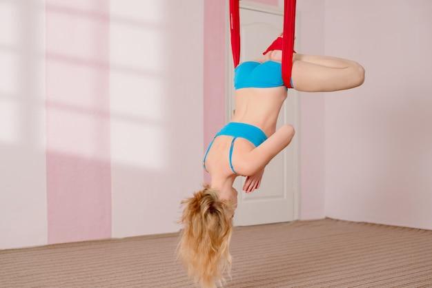Fliegen yoga. das mädchen führt luftyogaübungen durch Premium Fotos
