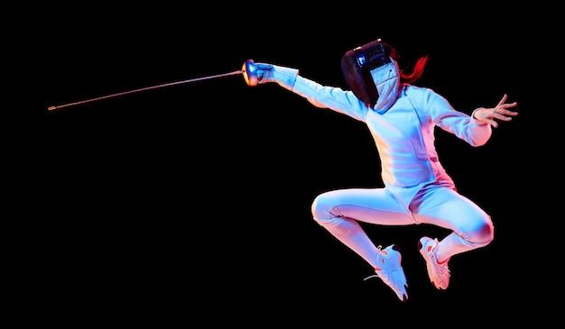 Fliegend. teenie-mädchen im fechtkostüm mit schwert in der hand lokalisiert auf schwarzer wand, neonlicht. junges model, das bewegung und aktion übt und trainiert. copyspace. sport, gesunder lebensstil. flyer. Kostenlose Fotos
