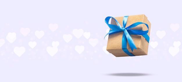 Fliegengeschenkbox auf einer hellen oberfläche mit herz formte bokeh. feiertagskonzept, geschenk, verkauf, hochzeit und geburtstag. . Premium Fotos