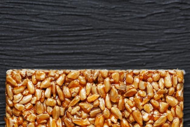 Fliesen-kozinaki aus sonnenblumenkernen. köstliche orientalische süßigkeiten gozinaki aus sonnenblumenkernen, sesam und erdnüssen, mit honig überzogen mit einer glänzenden glasur Premium Fotos