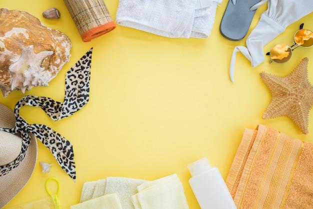 Flip flop in der nähe von handtuch mit seestern und badeanzug mit sonnenbrille zwischen hut und muschel Kostenlose Fotos