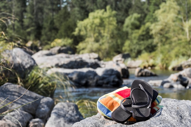 Flipflops an der steinküste in der nähe von wasser Kostenlose Fotos