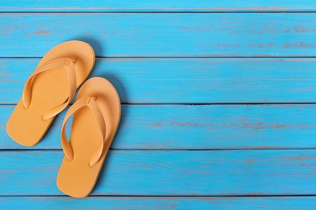 Flipflops auf altem verwittertem blauem strandholz Premium Fotos