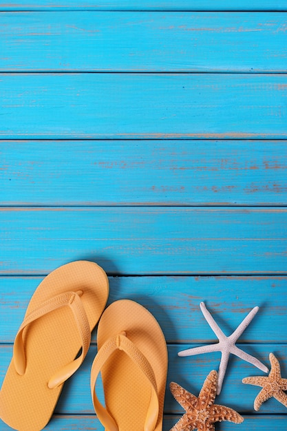 Flipflopsternfisch-sommerküste-blaue hölzerne hintergrundvertikale Premium Fotos