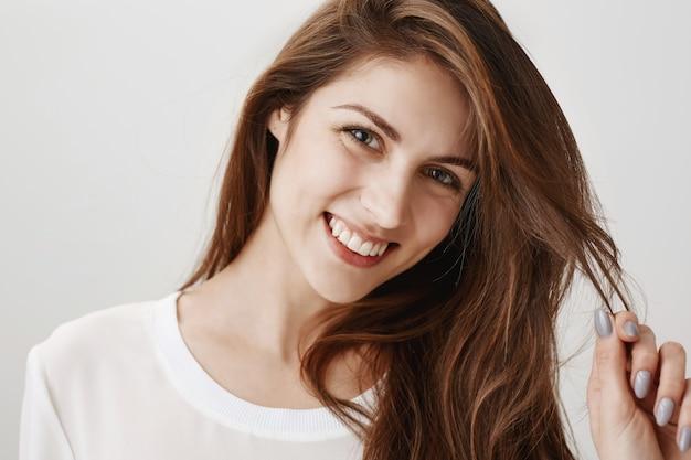Flirty glückliche frau, die mit haaren spielt und lächelt Kostenlose Fotos