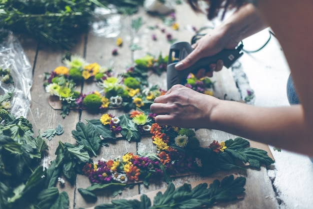 Florist, der blumendekoration mit buchstaben und kleber macht. natürliches licht in innenräumen mit geringer schärfentiefe Premium Fotos