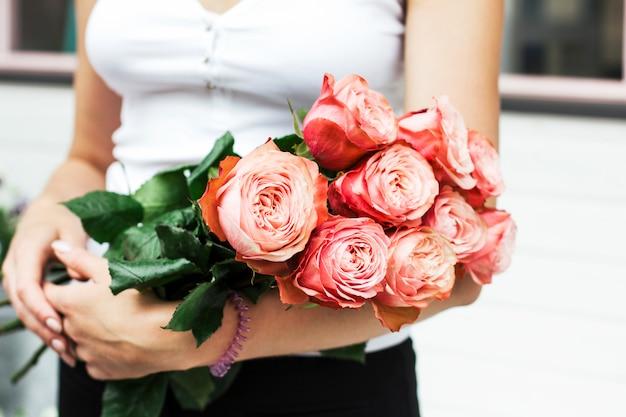 Florist der jungen frau, der blumenstrauß von rosa rosen an der straße hält Premium Fotos