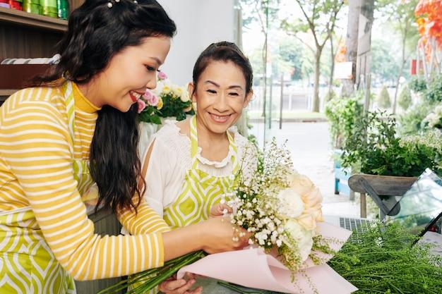 Florist, der mitarbeiter hilft, blumenstrauß in hellrosa papier zu wickeln Premium Fotos