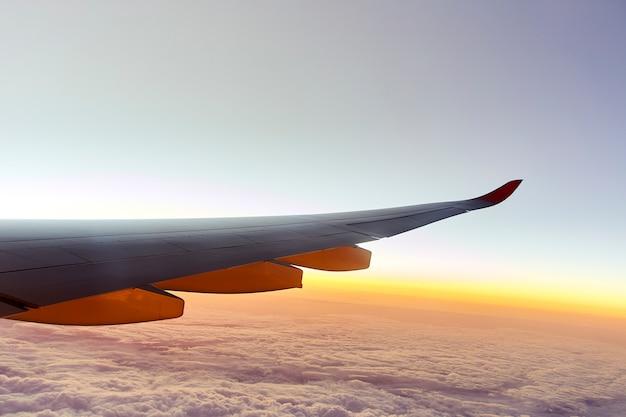 Flügel eines flugzeugs mit sonnenuntergang Premium Fotos