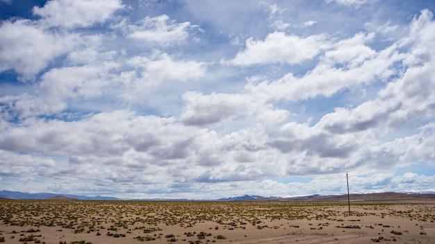 Flüssiger strom der großen höhe in der rauen unfruchtbaren landschaft mit szenischem drastischem himmel. weitwinkelansicht von oben genanntem bei 4000 m auf den andenhochländern, peru. Premium Fotos