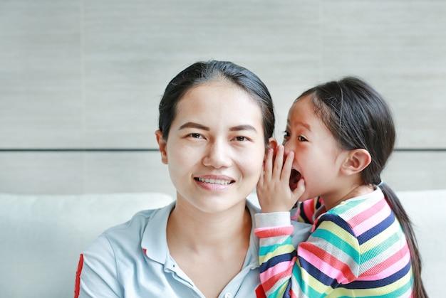 Flüsternder klatsch des kindermädchens etwas zum mutterohr. Premium Fotos