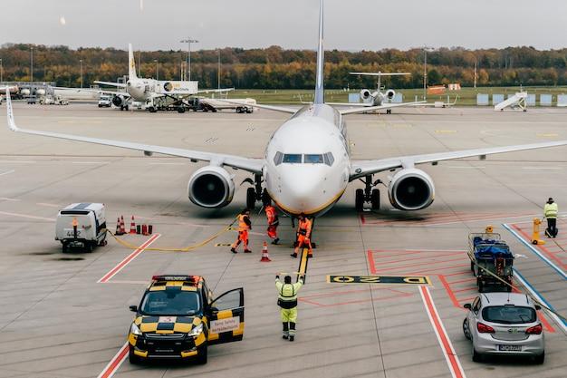 Flughafenangestellte warten gelandetes flugzeug. ansicht vom warteraum durch fenster an der rollbahn mit flugzeugen und wartungspersonal im arbeitsfluss Premium Fotos