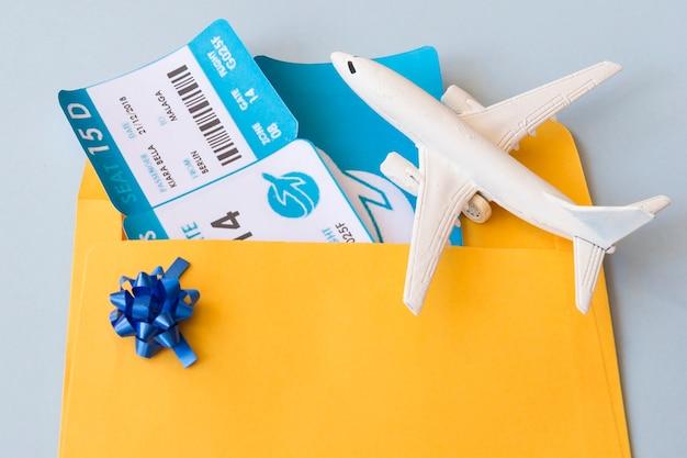 Flugtickets im dokumentenkasten nahe spielzeugflugzeugen Kostenlose Fotos