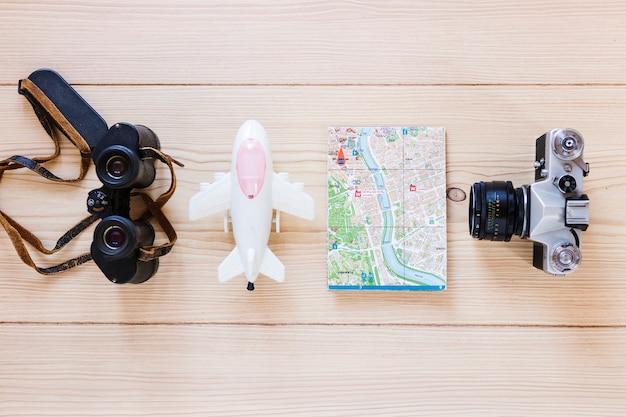 Flugzeug; fernglas; karte und kamera auf hölzernen hintergrund Kostenlose Fotos