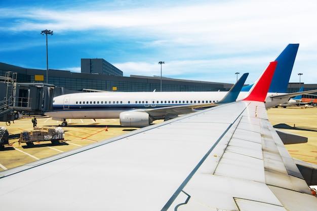 Flugzeug nahe dem terminal in einem flughafen bei dem sonnenuntergang. Premium Fotos