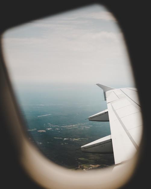 Flugzeugfenster mit blick auf die grünen felder oben und den rechten flügel Kostenlose Fotos