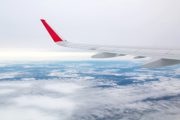Flugzeugflügel, der über die wolken fliegt Premium Fotos