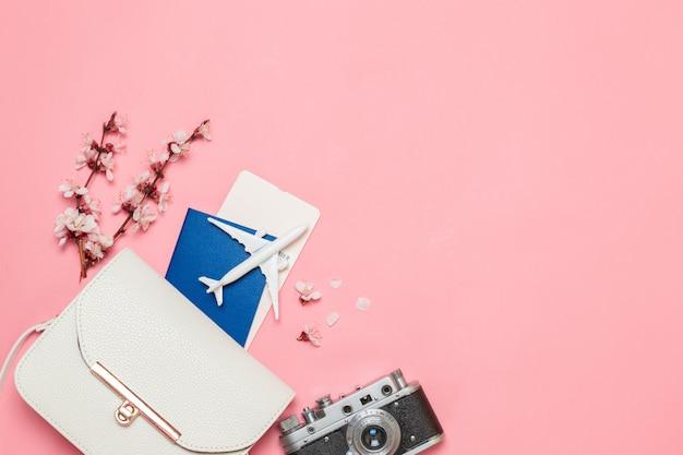 Flugzeugspielzeugmodell, alte kamera, karten und pass im flugzeug, handtasche auf einem rosa hintergrund. Premium Fotos