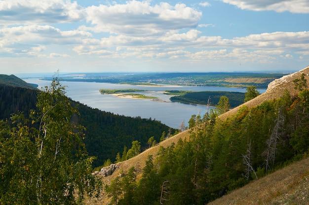 Fluss gegen den blauen himmel mit wolken und wäldern. Premium Fotos