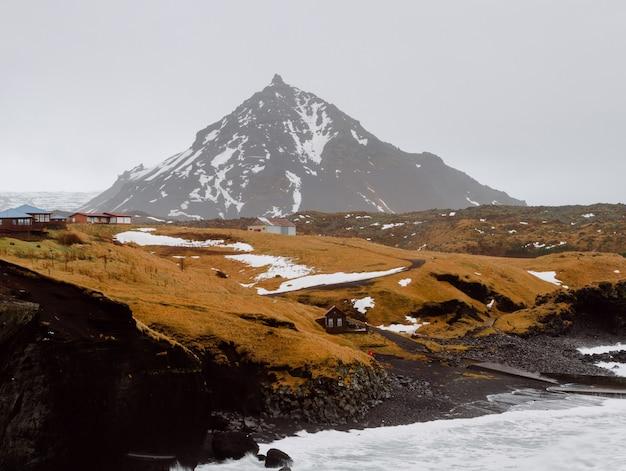 Fluss umgeben von felsen und hügeln bedeckt mit schnee und gras in einem dorf in island Kostenlose Fotos