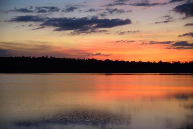 Fluss und berg im sonnenuntergang auf blauem und orange himmelhintergrund der nacht Premium Fotos