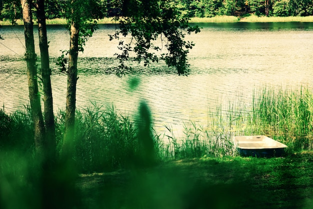 Flusslandschaft, baum, boot. reine natur hintergrund. sommer-konzept Premium Fotos