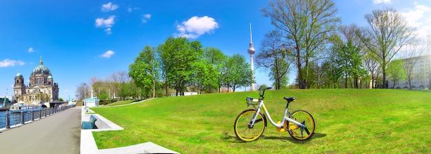 Flussufer in der mitte berlins mit dom links, fahrrad auf der grünen wiese und fernsehturm am alexanderplatz Premium Fotos
