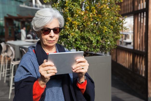 Fokussierte ältere dame, die elektronische karte konsultiert Kostenlose Fotos
