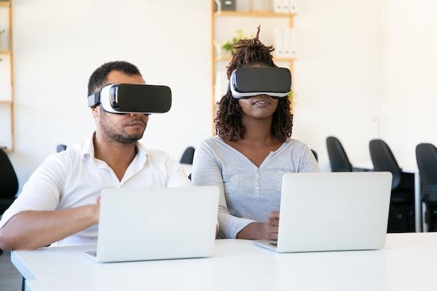 Fokussierte afroamerikanertester, die vr-gläser im büro tragen Kostenlose Fotos