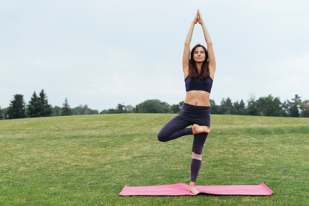 Fokussierte frau, die draußen yoga tut Kostenlose Fotos