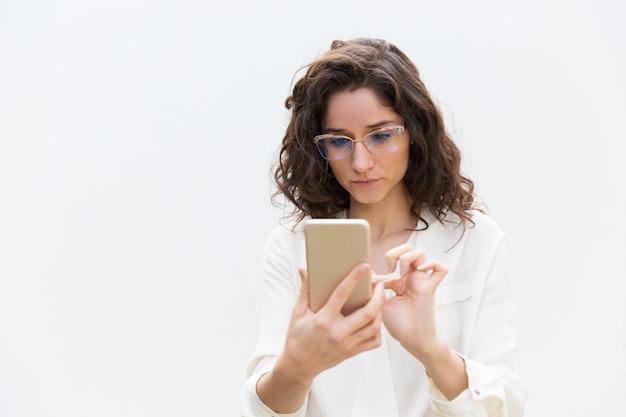 Fokussierte frau in den gläsern, die mitteilung, internet konsultierend simsen Kostenlose Fotos