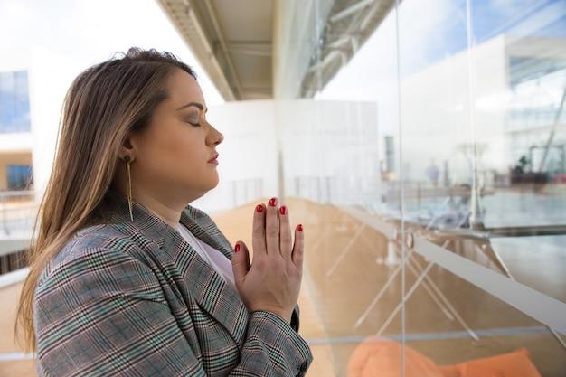 Fokussierte junge frau, die mit geschlossenen augen betet Kostenlose Fotos