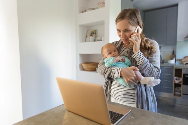 Fokussierte junge mutter, die baby hält Kostenlose Fotos