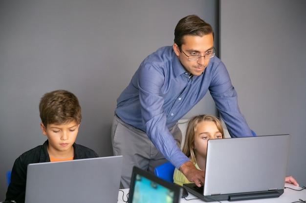 Fokussierte lehrerin hilft mädchen bei der aufgabe und tippt auf der tastatur Kostenlose Fotos