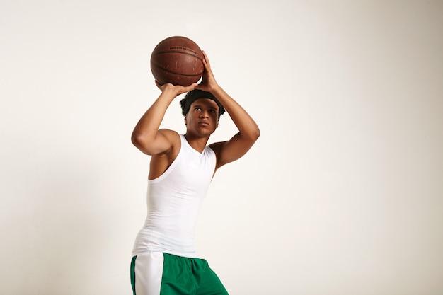 Fokussierte passform junger afroamerikanischer spieler im weißen und grünen basketball-outfit, das einen vintage-basketball wirft, der auf weiß isoliert wird Kostenlose Fotos