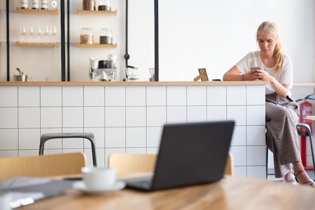 Fokussierte schöne blonde frau mit smartphone, sitzend an küchentheke im gemeinsamen arbeitsraum Kostenlose Fotos