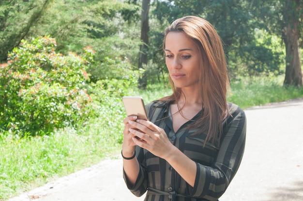 Fokussierte schreibensmitteilung geschäftsdame auf smartphone Kostenlose Fotos