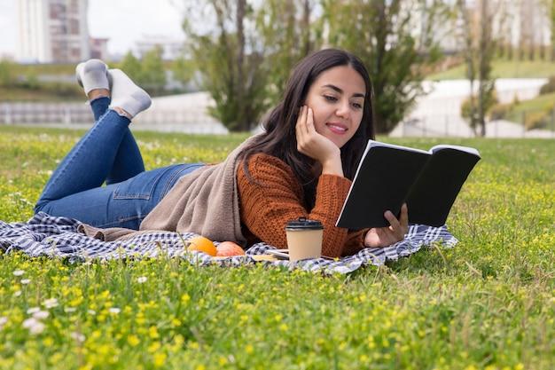 Fokussierte studentin, die draußen für test studiert Kostenlose Fotos