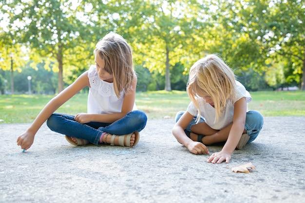 Fokussierte süße mädchen, die mit bunten kreidestücken sitzen und zeichnen. vorderansicht. konzept für kindheit und kreativität Kostenlose Fotos