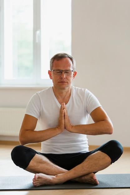 Fokussierter älterer mann, der yoga tut Kostenlose Fotos