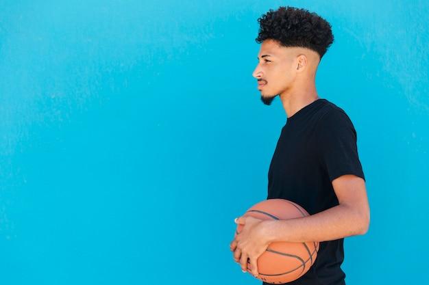 Fokussierter ethnischer spieler mit basketball Kostenlose Fotos