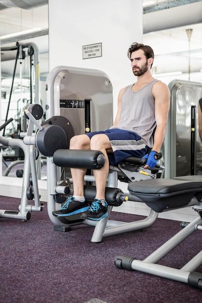 Fokussierter mann, der gewichtsmaschine für beine an der turnhalle verwendet Premium Fotos