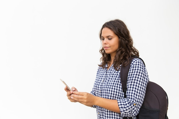 Fokussierter weiblicher tourist mit rucksack und mobiltelefon Kostenlose Fotos
