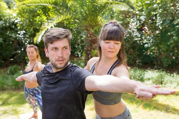 Fokussierter yogalehrer, der newby hilft Kostenlose Fotos