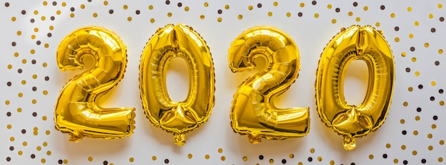Folie steigt goldene farbe in form von nr. 2020 im ballon auf Premium Fotos