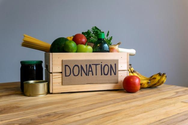 Food-spende-konzept. spendenbox mit gemüse, obst und anderen lebensmitteln zum spenden Premium Fotos