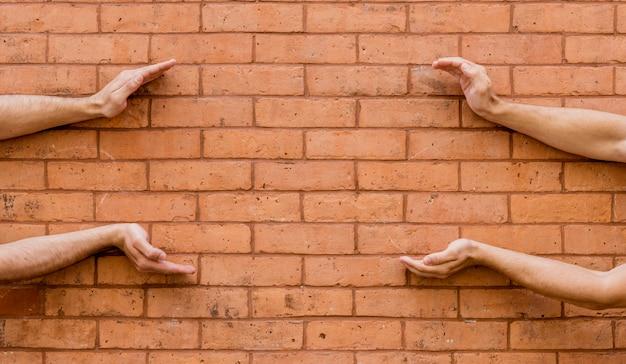Form gemacht durch menschliche hände auf backsteinmauer Kostenlose Fotos